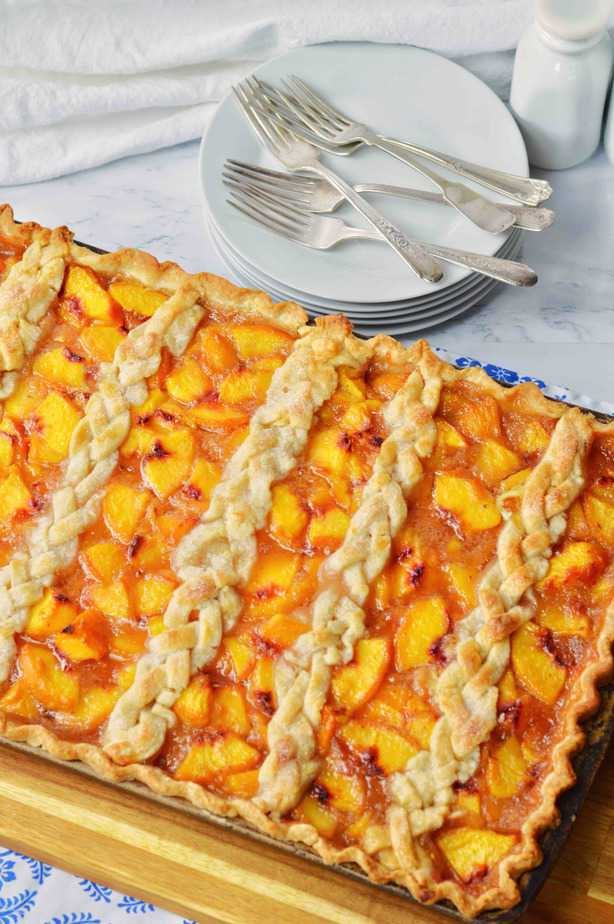 Full sheet pan of peach slab pie with braided top crust