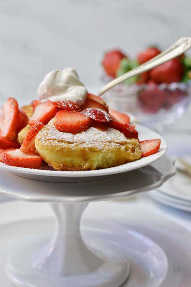 white pedestal plate filled with fluffy French toast, whipped cream and strawberries