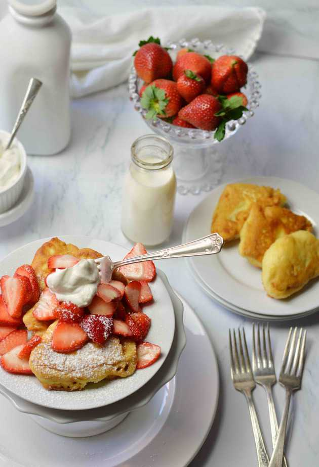plate of fresh fluffy French toast and plate of fluffy French toast topped with strawberries and whipped cream