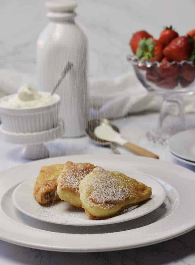 3 piece of fluffy French toast on plate dusted with powdered sugar.