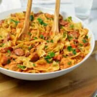 big white pasta bowl filled with colored peppers, chicken sausage, pasta and a red tomato cream sauce.