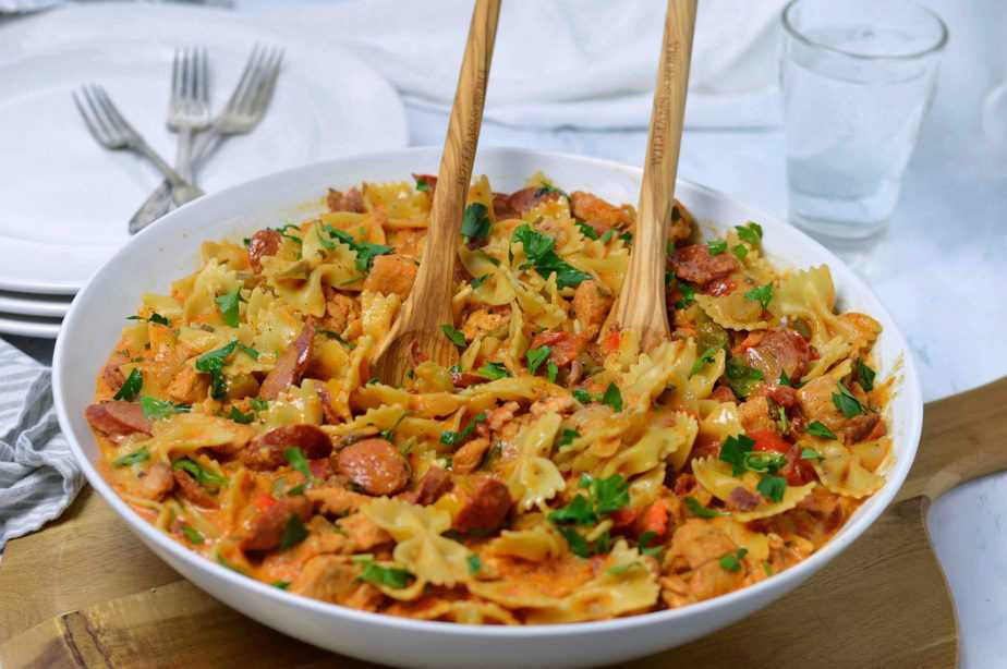 large white pasta bowl filled with jambalaya pasta and two wood serving pieces