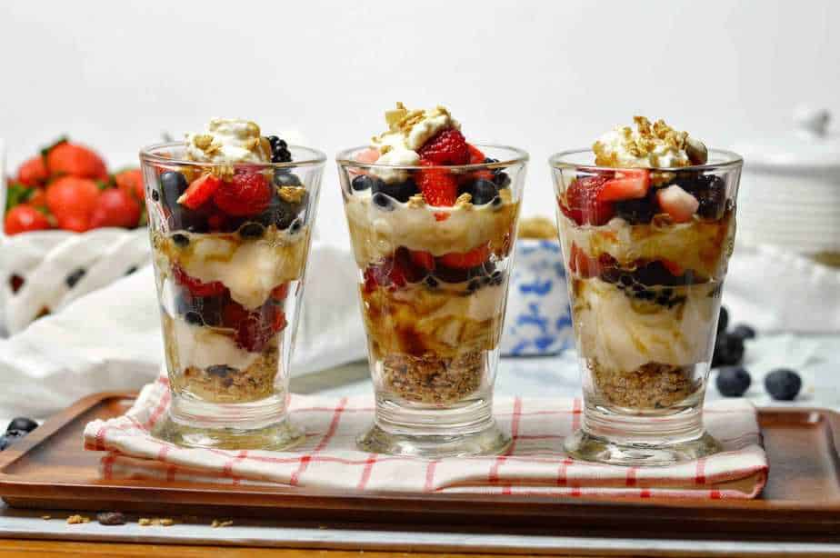 3 layered berry yogurt parfaits in clear glasses