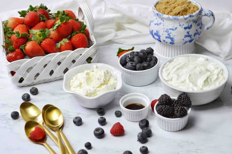 bowls filled with strawberries, blueberries, black berries, whipping cream, plain greek yogurt, vanilla and brown sugar for berry yogurt parfats
