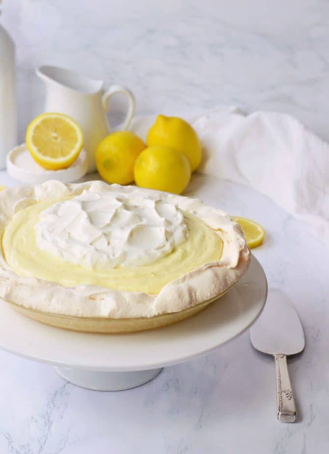 lemon cloud pie with white pitcher and lemons behind