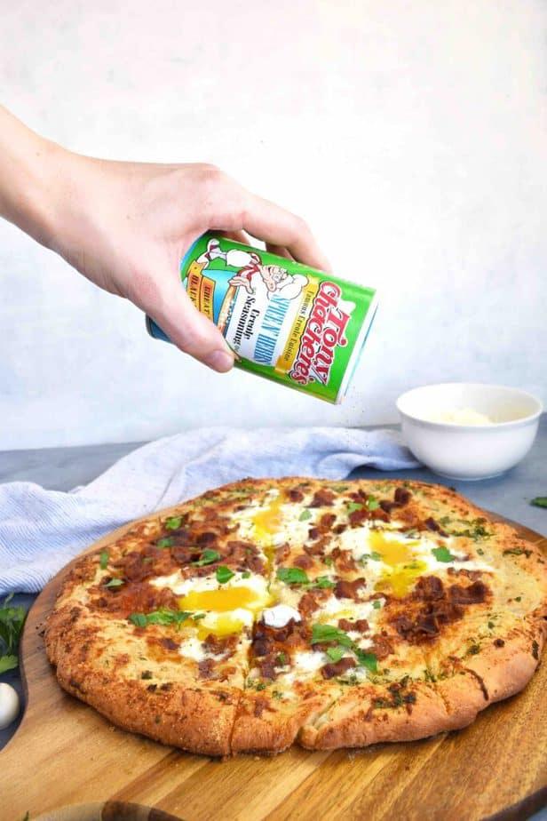 tony's seasoning shaker being shook over top of pizza