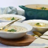 3 white bowls of white chicken chili with gold spoons