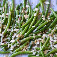 lemon garlic roasted green beans on baking sheet with almonds