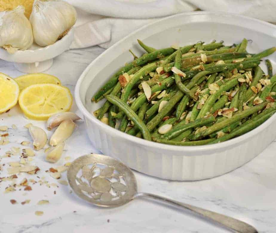 white dish with roasted lemon garlic green beans and almonds