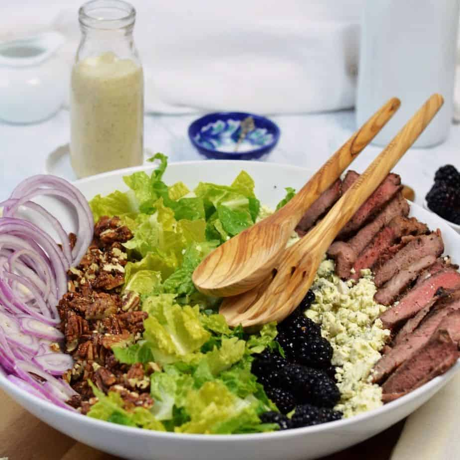 large white bowl with separate ingredients for steak salad and bottle of blue cheese vinaigrette. featured image