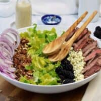 large white bowl with ingredients for steak salad