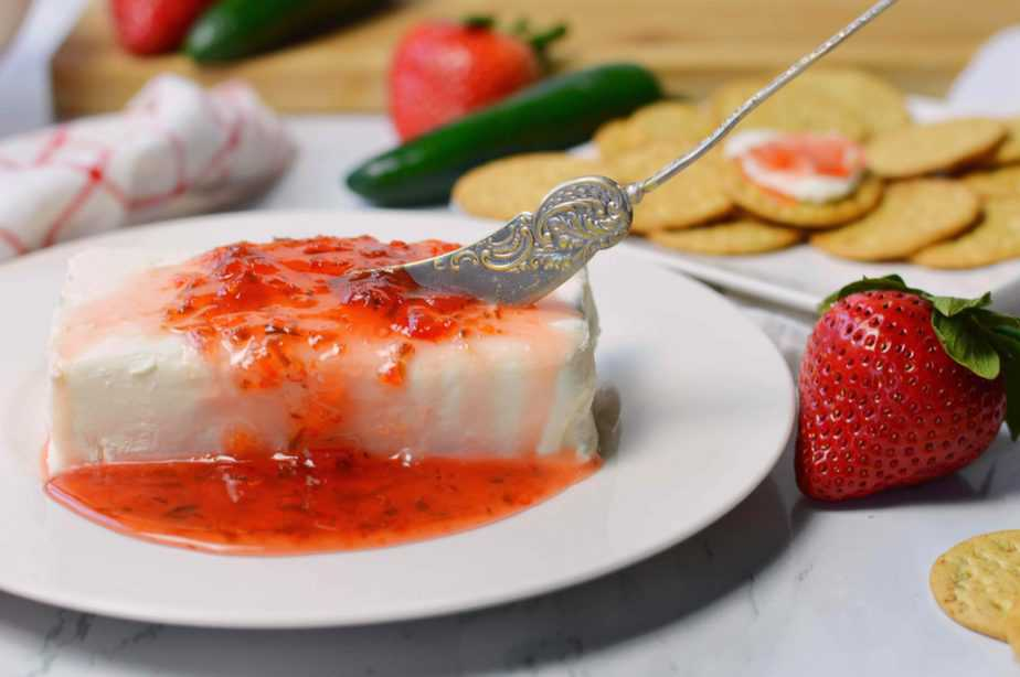 white plate with brick of cream cheese topped with jalapeno strawberry jam and a serving knife