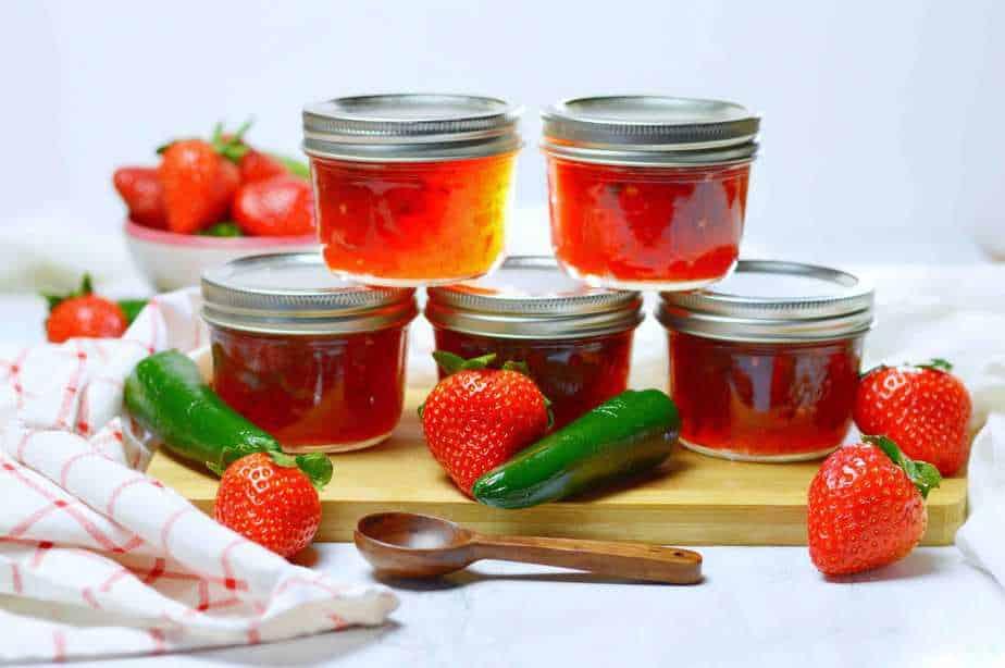 5 jars of jalapeno strawberry jam arranged with fresh strawberries and jalapenos