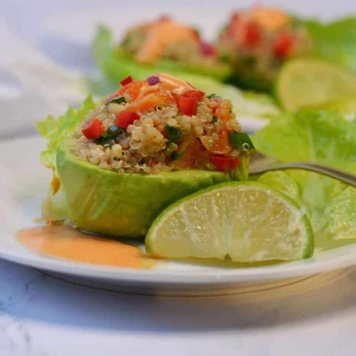 fresh avocado stuffed with quinoa salad and habanero sauce on white plate