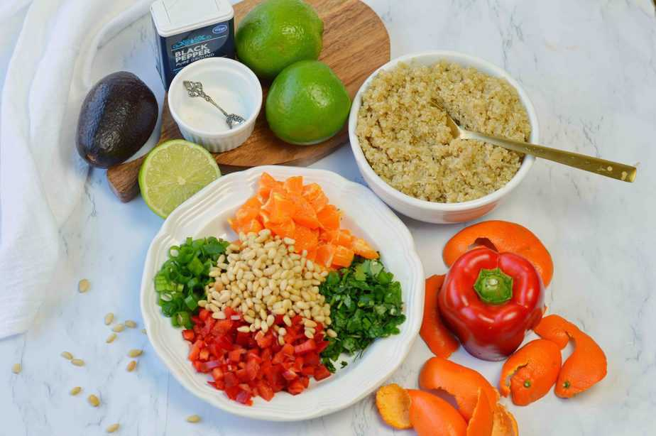 bowl of quinoa, platter of chopped red pepper, tangerine pieces, green onion and cilantro plus other ingredients for avocado quinoa salad