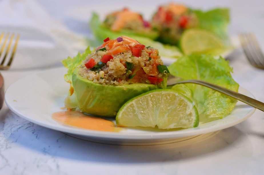 one avocado half stuffed with quinoa salad on white plate with lime
