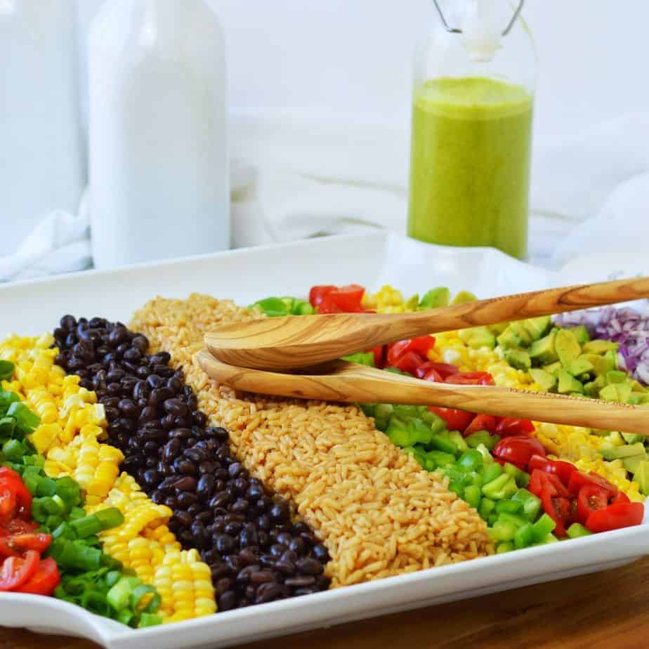 white platter with rows of vegetables for cowboy rice salad