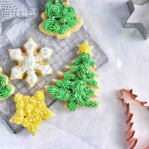 frosted sugar cookies in tree and star shapes on cooling rack