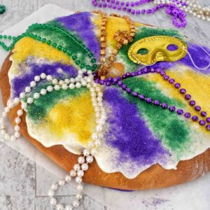 king cake with beads and colored sugar on top