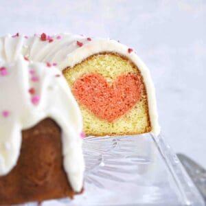 sliced open bundt cake on cake stand showing heart inside